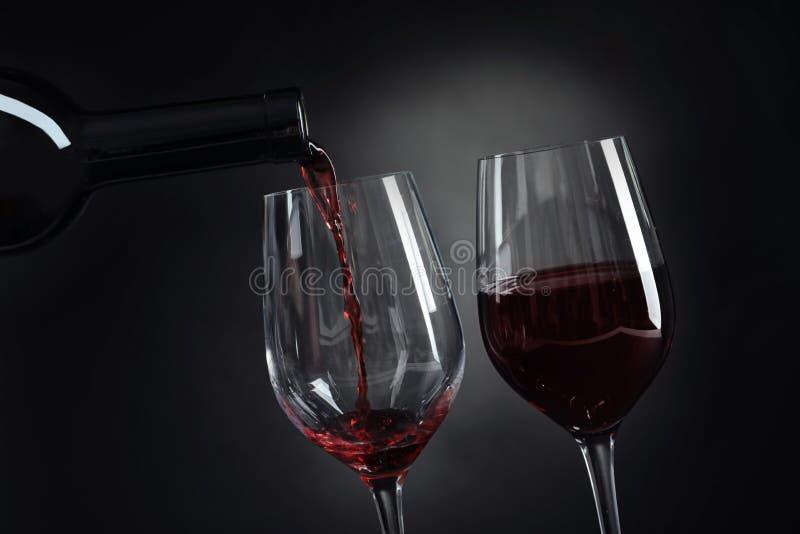 Vinho tinto delicioso de derramamento no vidro imagens de stock