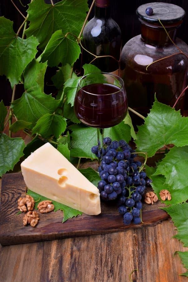 Vinho tinto em um vidro cercado pelos aperitivos: Queijo de Maasdam, nozes e um grupo de uvas de Isabella imagem de stock