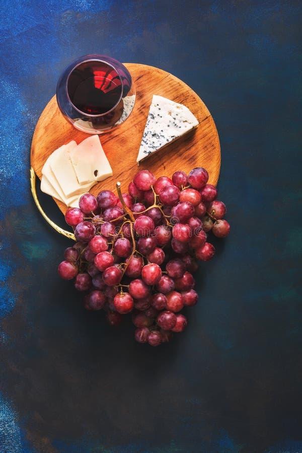 Vinho tinto em um vidro, em uvas e em queijo com um molde em um fundo azul Vista superior, espaço para o texto imagem de stock royalty free