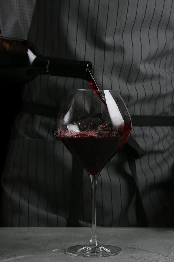 Vinho tinto que derrama no vidro barman no conceito do gar?om no fundo preto imagens de stock royalty free