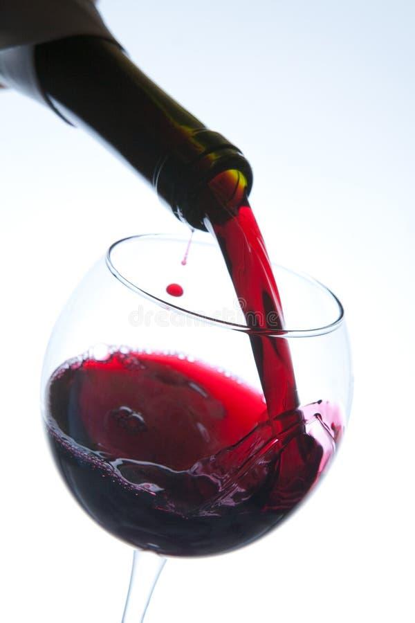 Vinho tinto que derrama no vidro de vinho imagem de stock royalty free