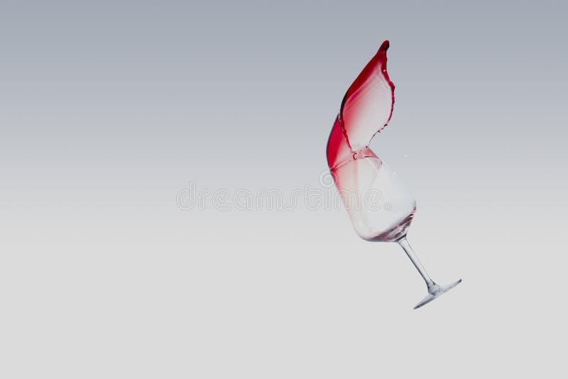 Vinho tinto que espirra fora de um vidro, isolado sobre o fundo branco foto de stock