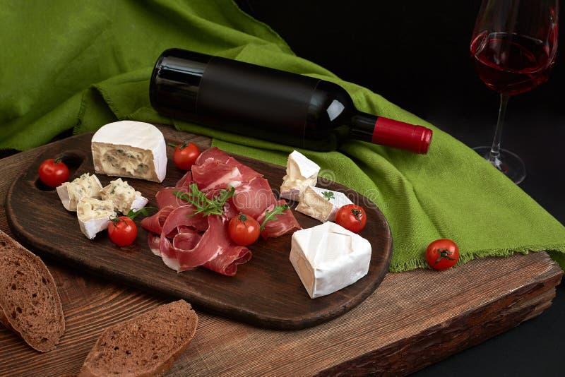 Vinho tinto, queijo, tomate de cereja, pão e prosciutto na placa de madeira sobre o contexto preto, vista superior, espaço da cóp foto de stock