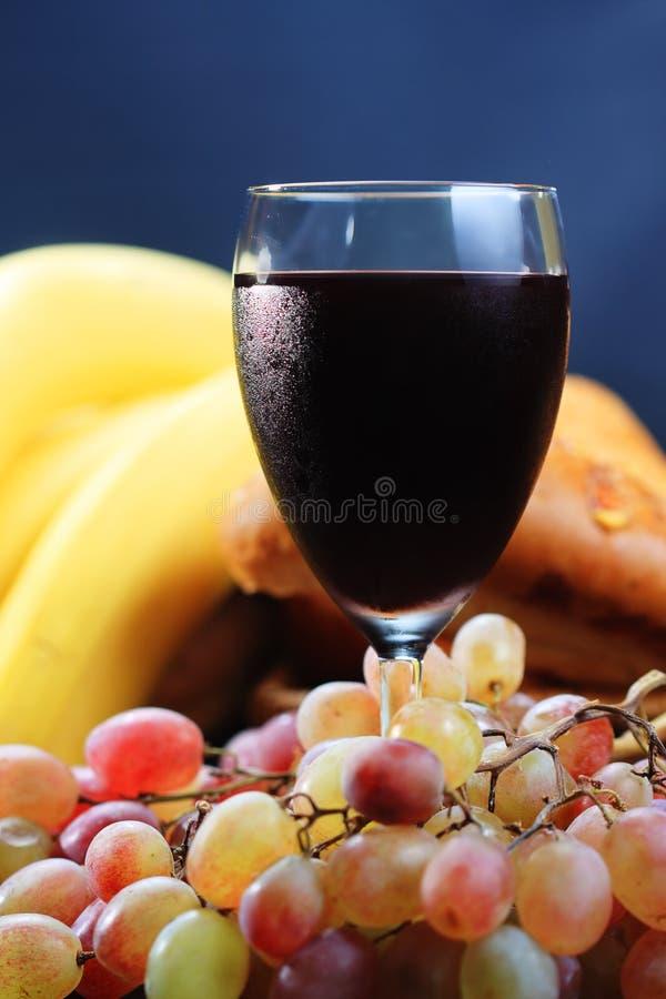 Vinho vermelho com as bananas no fundo foto de stock royalty free