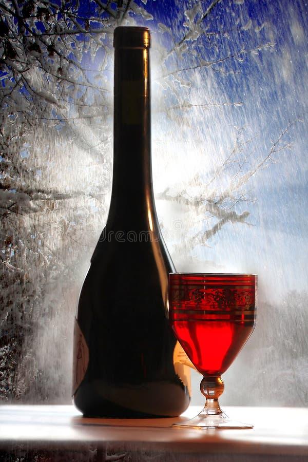 Vinho vermelho com vidro no fundo do inverno foto de stock royalty free