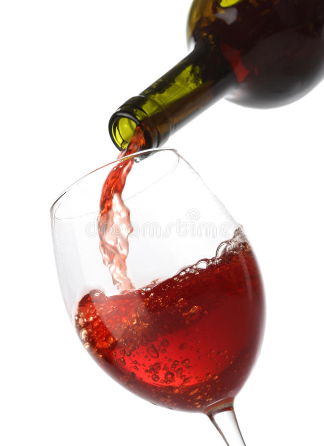 Vinho vermelho de derramamento em um vidro imagem de stock