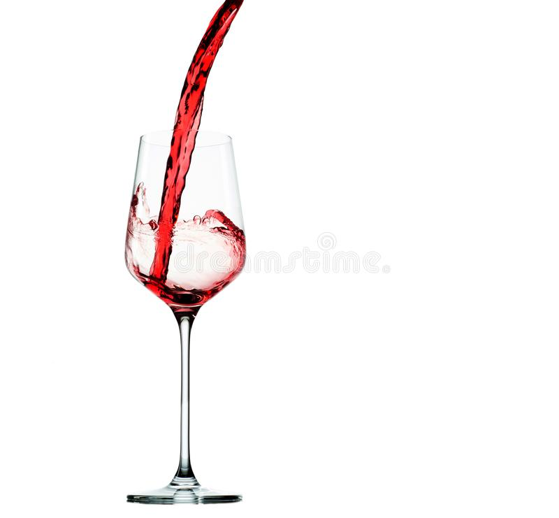 Vinho vermelho de derramamento no cálice de vidro isolado no branco fotografia de stock royalty free