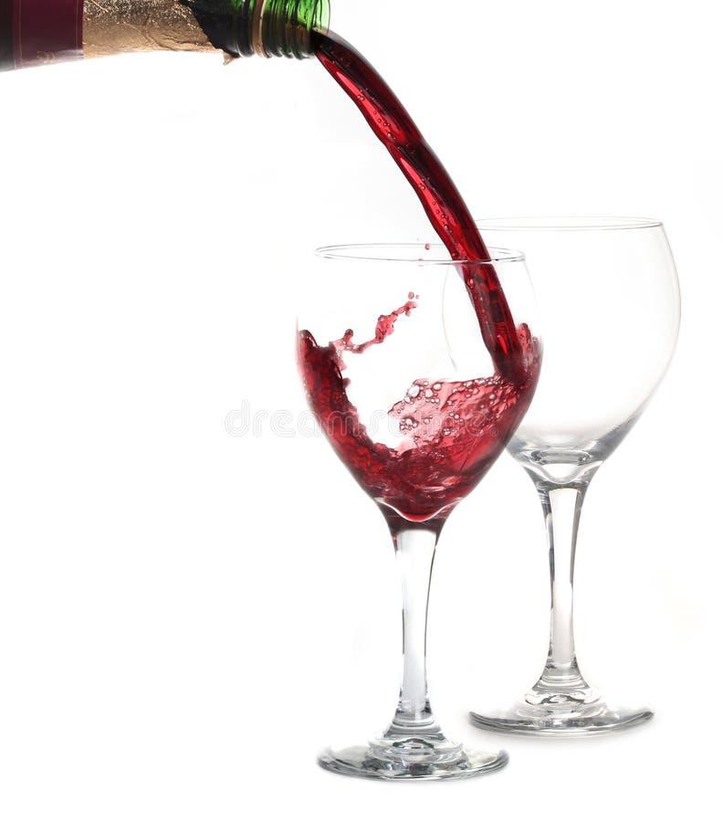 Vinho vermelho do Merlot que derrama em um vidro foto de stock