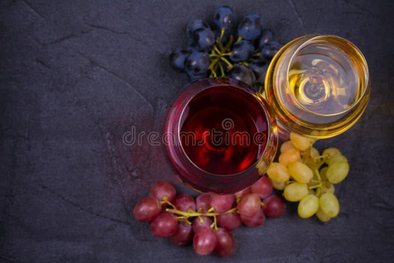 Vinho vermelho e branco em vidros de vinho com as uvas no fundo de pedra escuro com espaço da cópia fotos de stock
