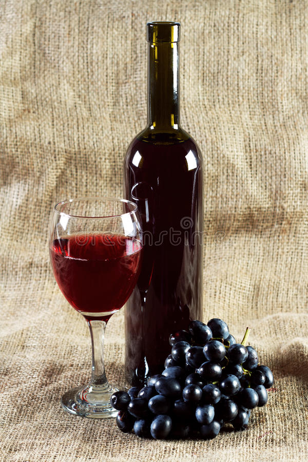 Vinho vermelho e uvas no fundo do vintage fotografia de stock royalty free