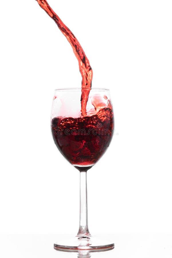 Vinho vermelho que derrama em um vidro imagens de stock