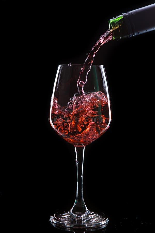 Vinho vermelho que derrama em um vidro de vinho foto de stock royalty free