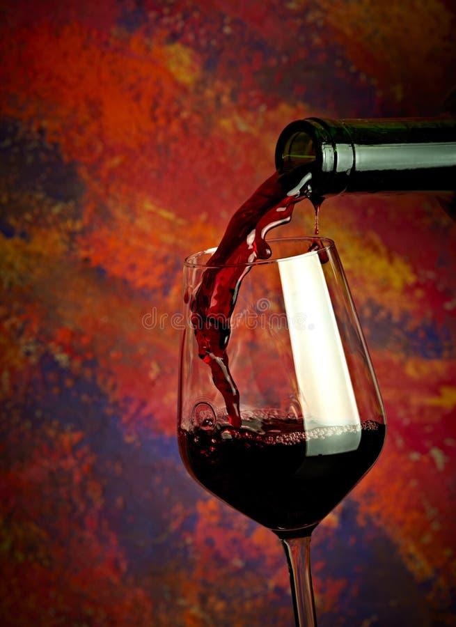 Vinho vermelho que derrama no vidro fotos de stock