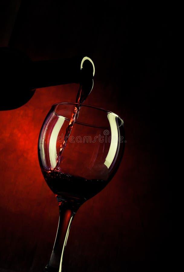 Vinho vermelho que derrama para baixo fotografia de stock