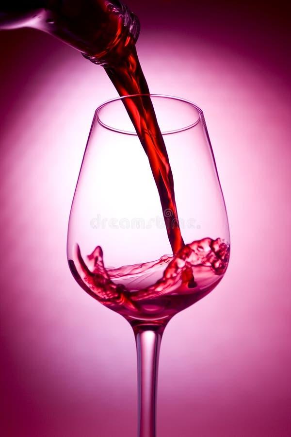 Vinho vermelho que está sendo derramado imagens de stock