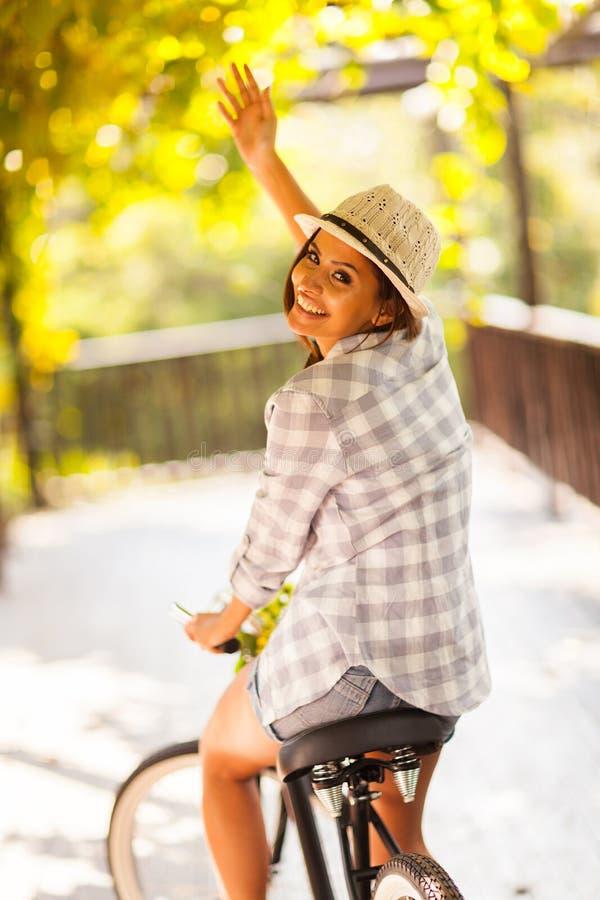 Vinka för kvinnacykel fotografering för bildbyråer