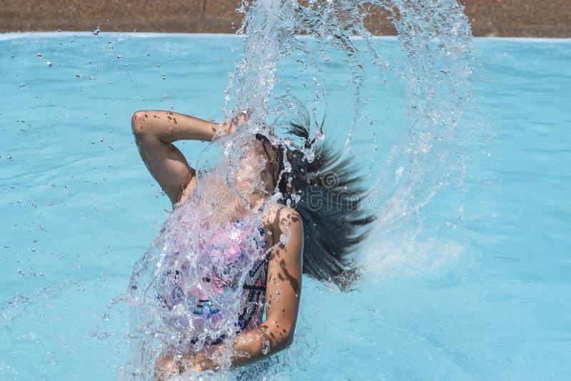Vinka frysningen på en flicka som plaskar havsvattnet med hennes hår royaltyfria bilder