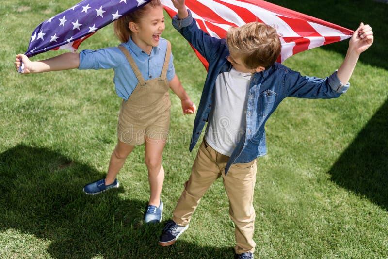 Vinkande amerikanska flaggan för förtjusande lycklig syskongrupp fotografering för bildbyråer
