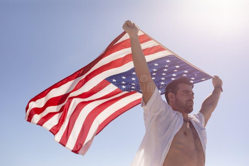 Vinkande amerikanska flaggan för ung man på stranden i solskenet arkivbild