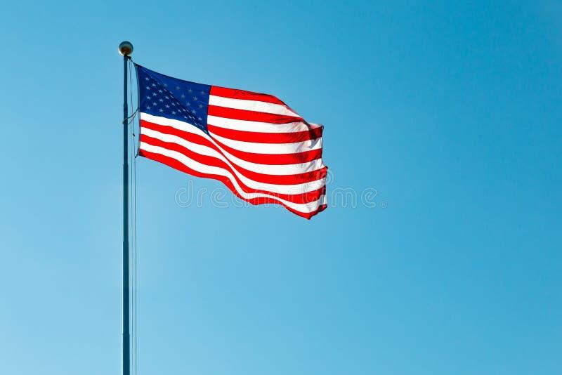 Vinkande amerikanska flaggan med blå himmel arkivfoton
