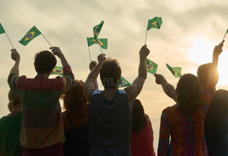 Vinkande brasilianflaggor för grupp människor arkivbild