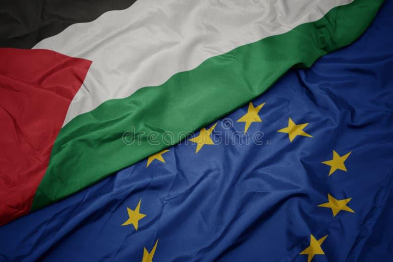 vinkande färgrik flagga av europeisk union och flagga av Palestina royaltyfria bilder