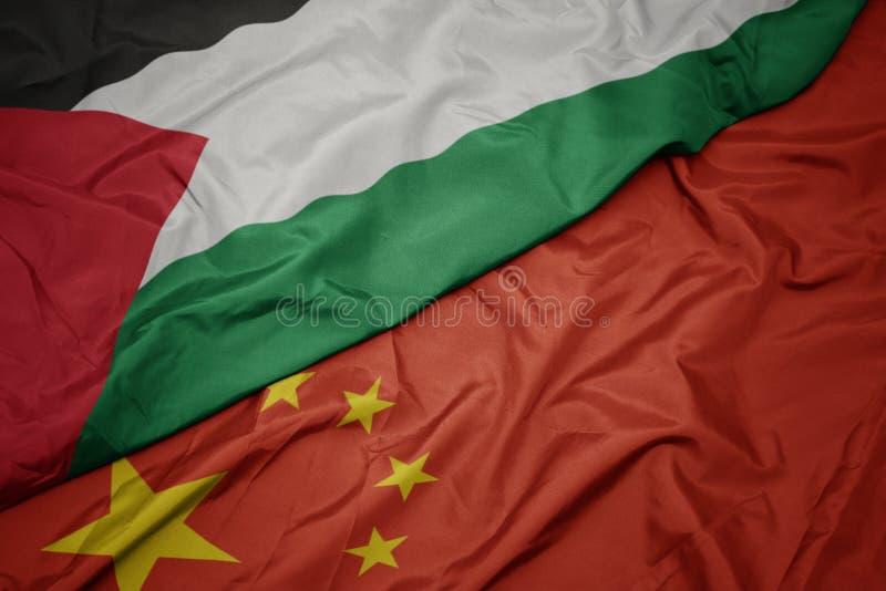 vinkande färgrik flagga av porslinet och nationsflagga av Palestina royaltyfria foton