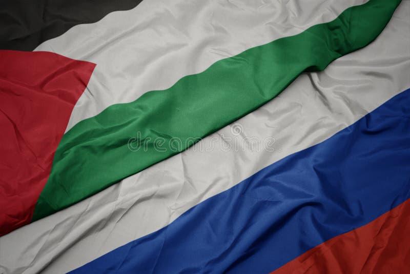 vinkande färgrik flagga av Ryssland och nationsflagga av Palestina arkivbild