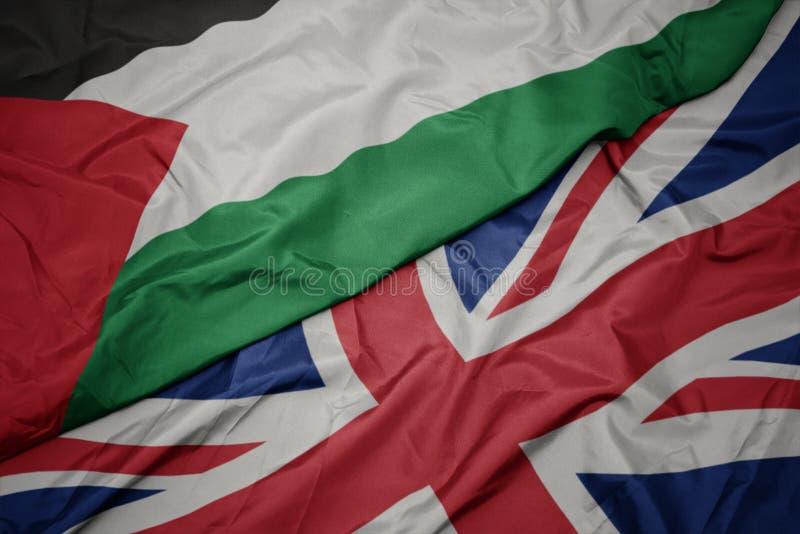 vinkande färgrik flagga av Storbritannien och nationsflagga av Palestina arkivfoto