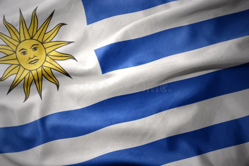 Vinkande färgrik flagga av Uruguay arkivbilder