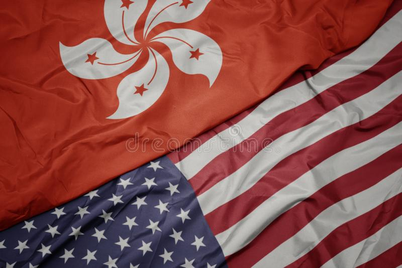 vinkande färgrik flagga av USA och nationsflagga av Hong Kong royaltyfri foto