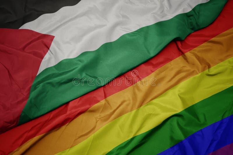 vinkande färgrik glad regnbågeflagga och nationsflagga av Palestina arkivfoton
