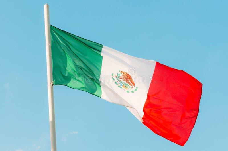 Vinkande färgrik Mexico flagga på blå himmel arkivfoton