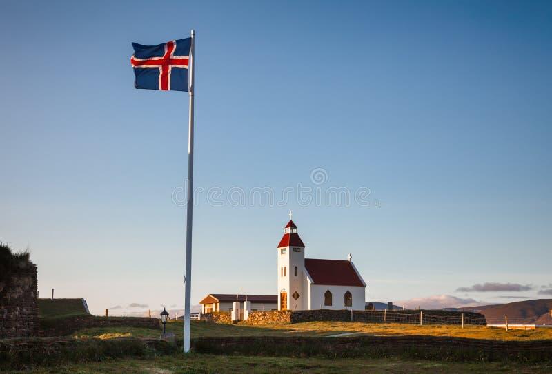 Vinkande flagga av Island på den vita kyrkliga Modrudalur lantgården östliga Island Skandinavien fotografering för bildbyråer