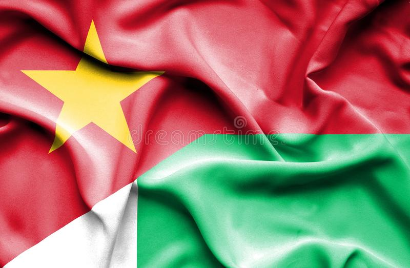 Vinkande flagga av Madagascar och Vietnam stock illustrationer