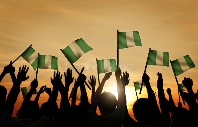 Vinkande flagga för grupp människor av Nigeria royaltyfria bilder