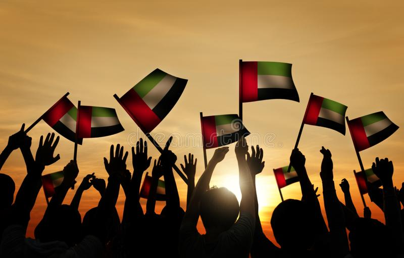 Vinkande flagga för grupp människor av UAE i tillbaka Lit royaltyfri bild