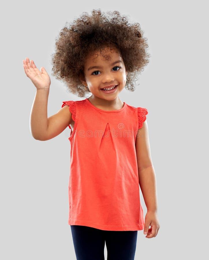 Vinkande hand för lycklig liten afrikansk amerikanflicka arkivfoto