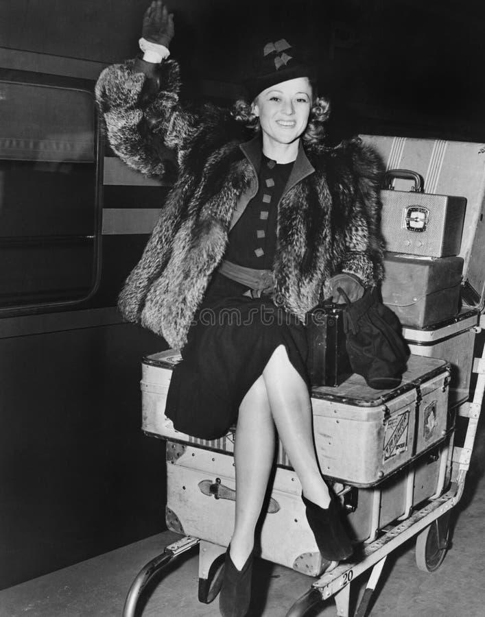 Vinkande kvinnasammanträde på högen av bagage (alla visade personer inte är längre uppehälle, och inget gods finns Leverantörgara arkivfoton