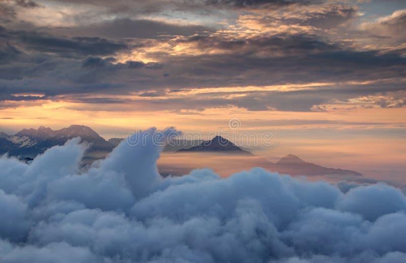Vinkande moln och ojämna berg i röd glödande höstmist arkivbild