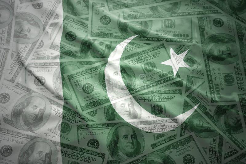 vinkande pakistansk flagga på en amerikansk dollarpengarbakgrund royaltyfri foto
