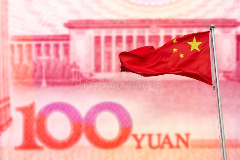 Vinkande röd nationsflagga av Kina mot hundra kinesiska yuansedelbakgrund bakgrundsbegreppet bantar guld- ?ggfinans arkivbilder