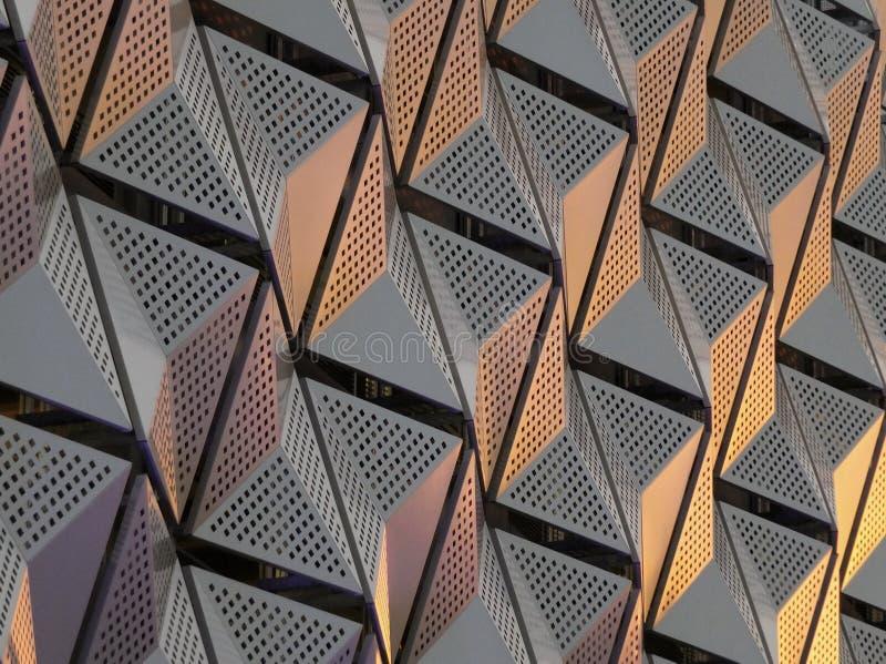 Vinkelformig geometrisk cladding för modernt stål med färgsignaler och perforerad mönstrad design arkivbild