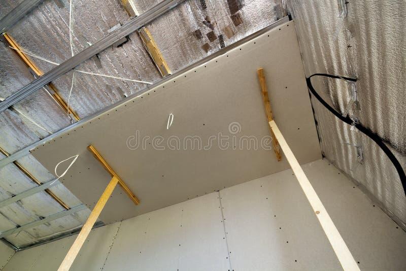 Vinkelsikt av oavslutat rum under konstruktion och renovering med folie för silveraluminiumisolering på väggar och tak och royaltyfri foto