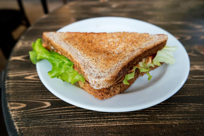 Vinkelsikt av triangelklubbhussmörgåsen på plattan royaltyfri fotografi