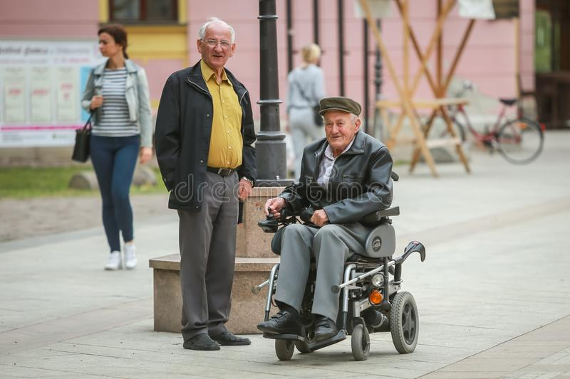 Vinkovci town in Croatia. VINKOVCI, CROATIA - MAY 14, 2018 : Close up of two senior men while one is in the wheelchairs and driving in the street of Vinkovci stock photography