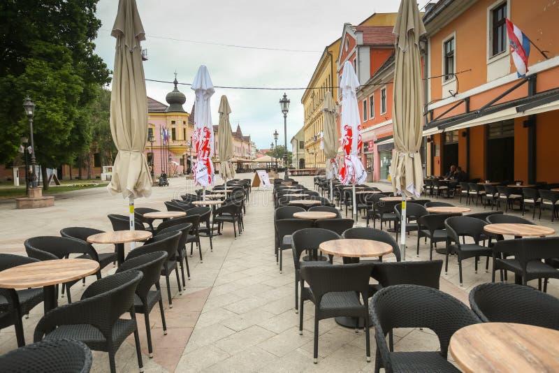 Vinkovci town in Croatia. VINKOVCI, CROATIA - MAY 14, 2018 : An empty terrace of coffee bar in city center of Vinkovci, Croatia stock images