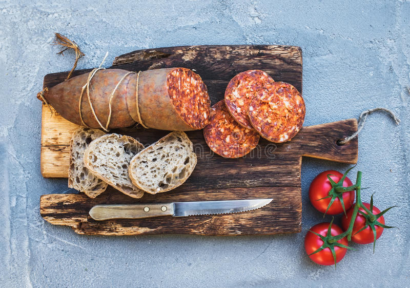 Vinmellanmåluppsättning Ungersk korv för mangalicagrisköttsalami, lantligt bröd och nya tomater på mörkt träbräde över a royaltyfria bilder