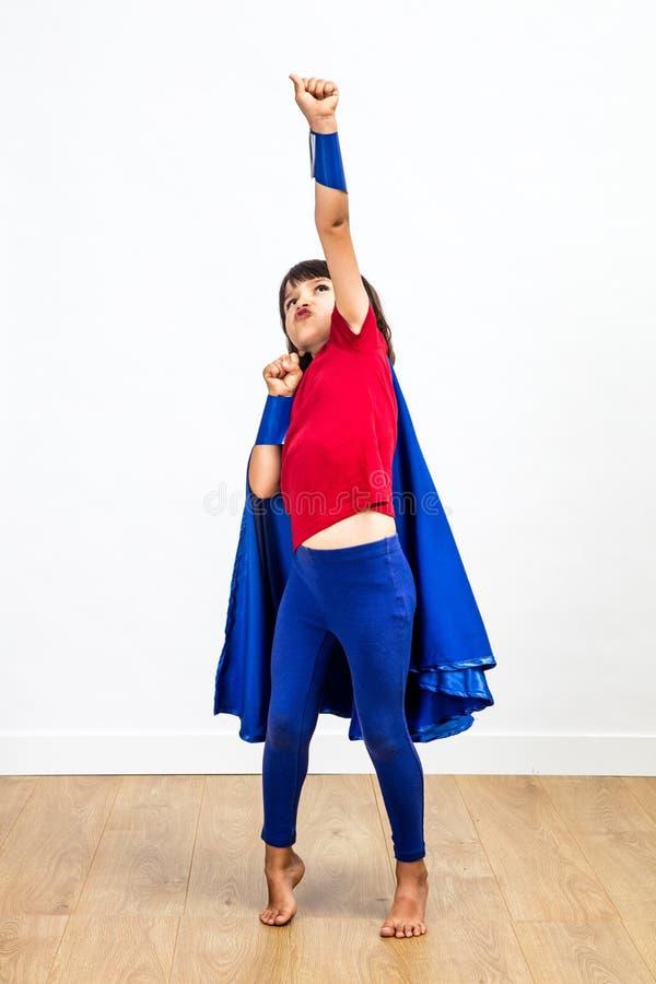Vinnande barn för toppen hjälte som spelar med en lyftt kraftig arm royaltyfria bilder