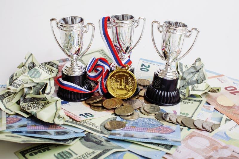 Vinnande begrepp för sport: tre koppar bland olika valutor euroet, dollaren, rubl, guldmedalj förlägger först arkivbilder